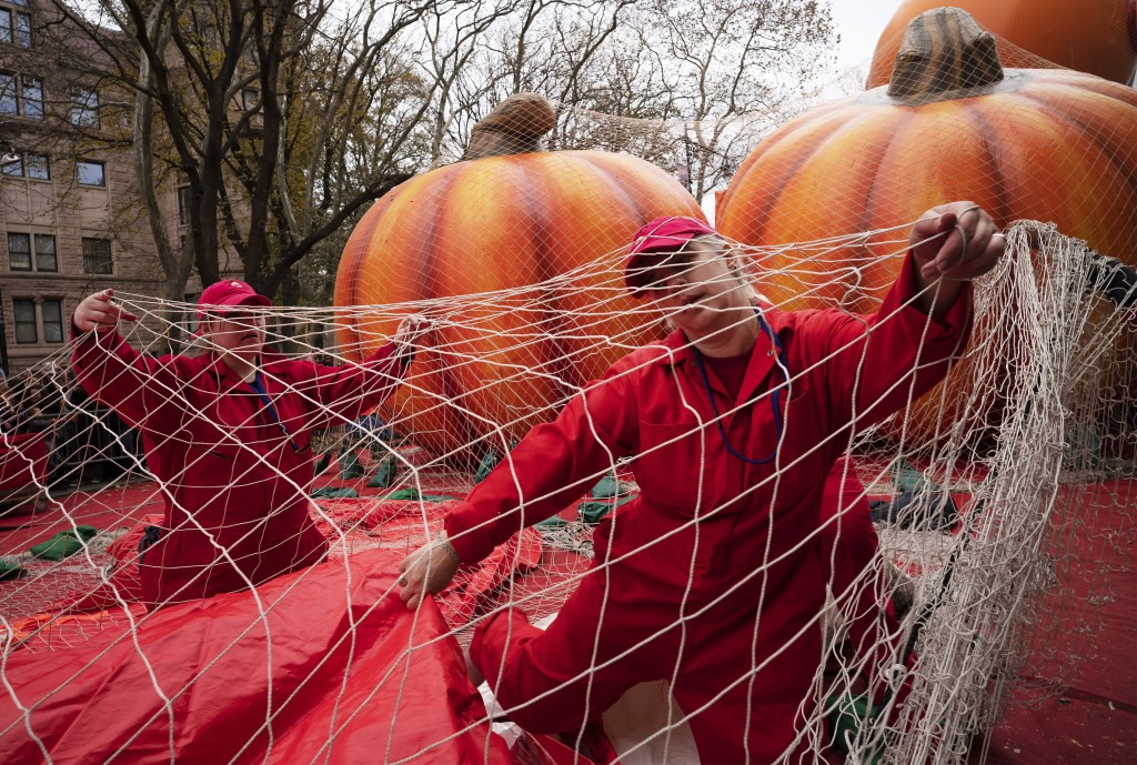 Michele Schleibaum, right, arranges protective netting on the Power Rangers Mighty Morphin Red Ranger balloon as it is inflated, Wednesday, Nov. 27, 2...