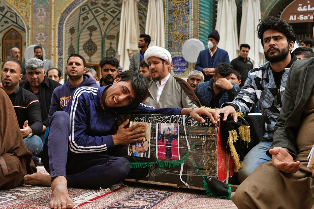 Mourners grieve over the coffin of Mehdi Kadim, 17, a protester killed during anti-government demonstrations, during his funeral in Najaf, Iraq, Frida...