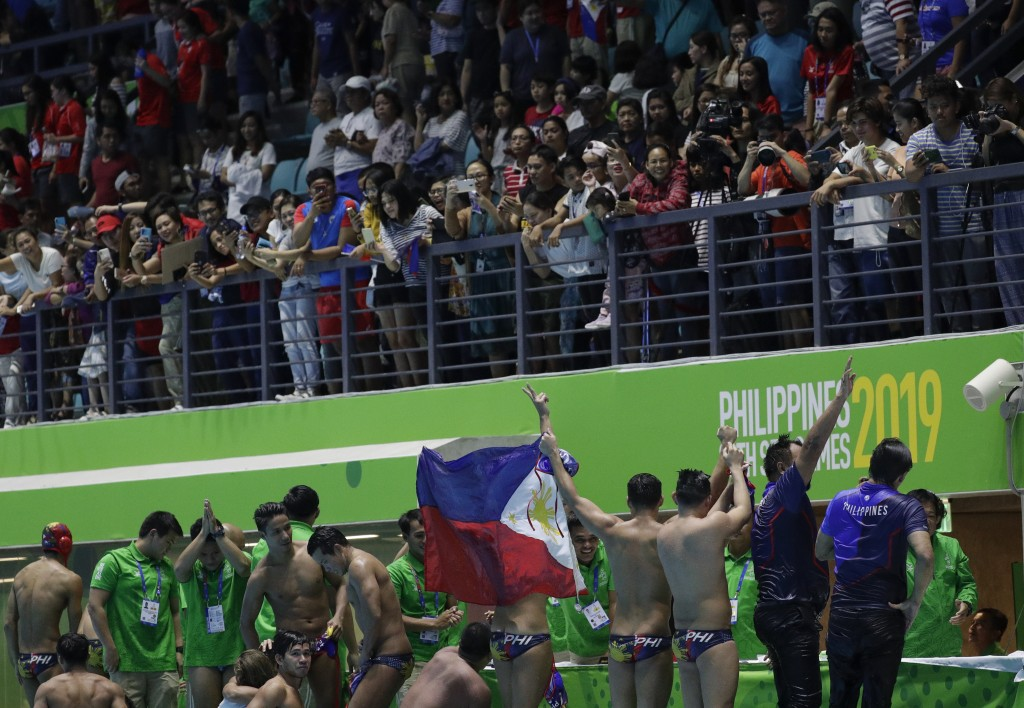 Philippines' water polo team carry the national flag as they acknowledge the cheers from the crowd after their game against Singapore at the 30th Sout...