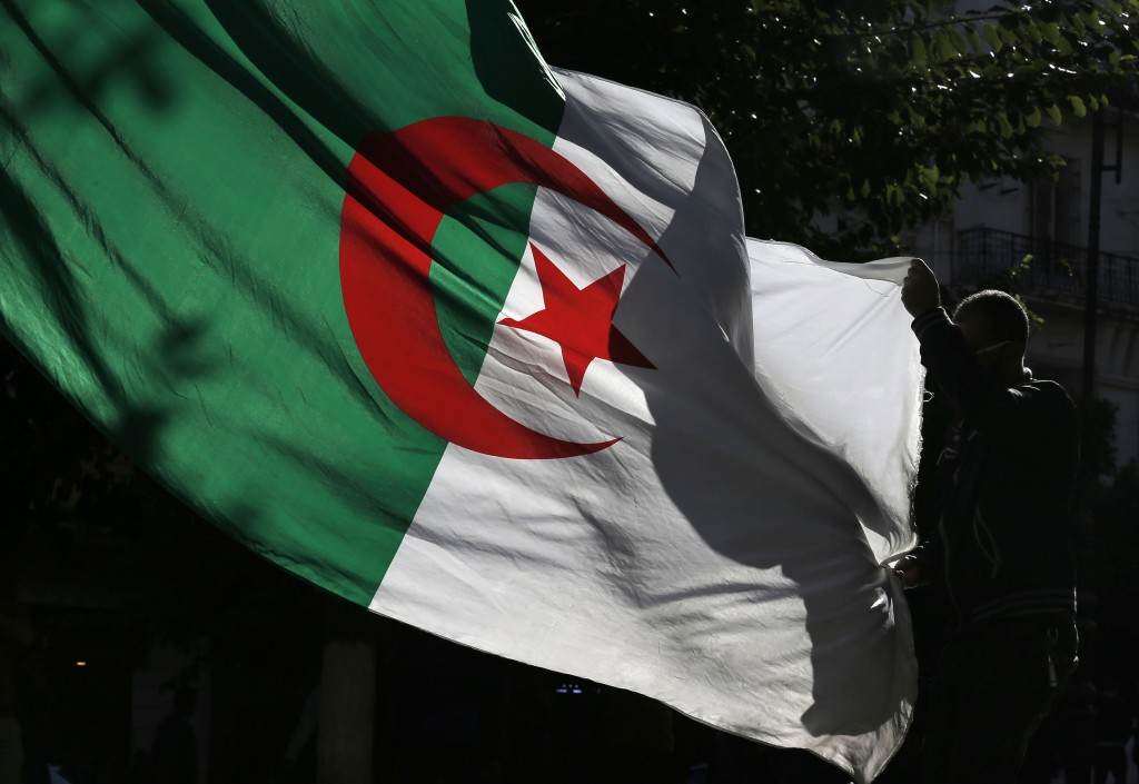 An Algerian demonstrator holds the Algerian national flag as he stage a protest against the government in Algiers, Algeria, Friday, Nov.29, 2019. Thou...