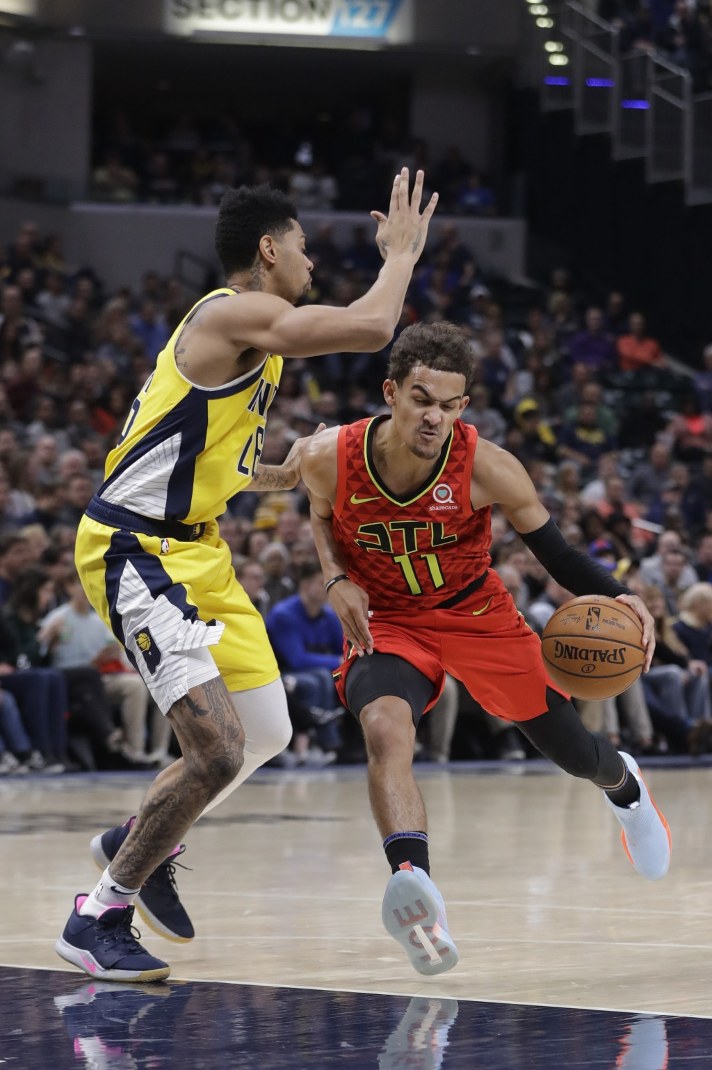 Atlanta Hawks' Trae Young, right, is fouled by Indiana Pacers' Jeremy Lamb, left, during the first half of an NBA basketball game, Friday, Nov. 29, 20...