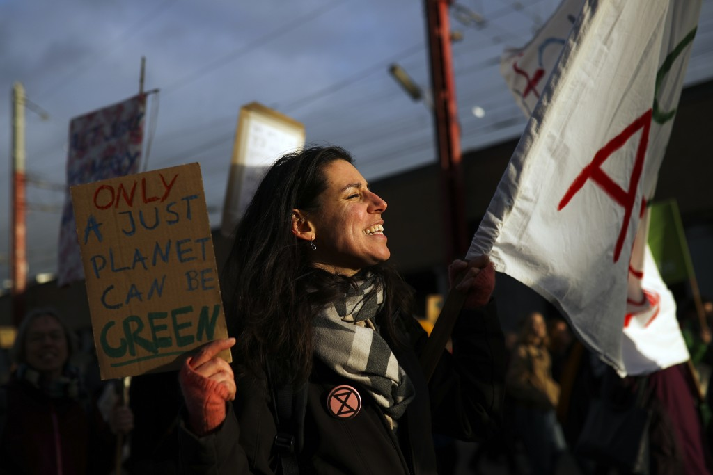 A woman shouts slogans as she marches with others during a worldwide protest demanding action on climate change in Brussels, Friday, Nov. 29, 2019. (A...