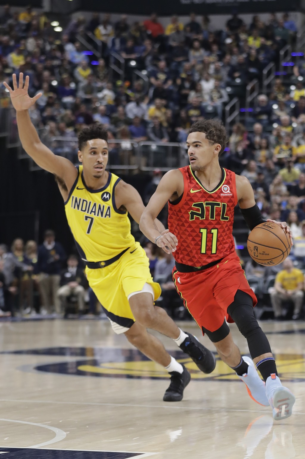 Atlanta Hawks' Trae Young (11) is defended by Indiana Pacers' Malcolm Brogdon (7) during the first half of an NBA basketball game, Friday, Nov. 29, 20...