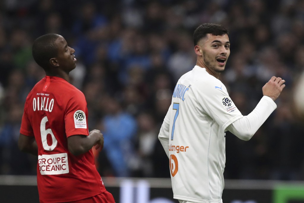 Marseille's Nemanja Radonjic celebrates ahead of Brest's Ibrahima Diallo after scoring his side's second goal during the French League One soccer matc...