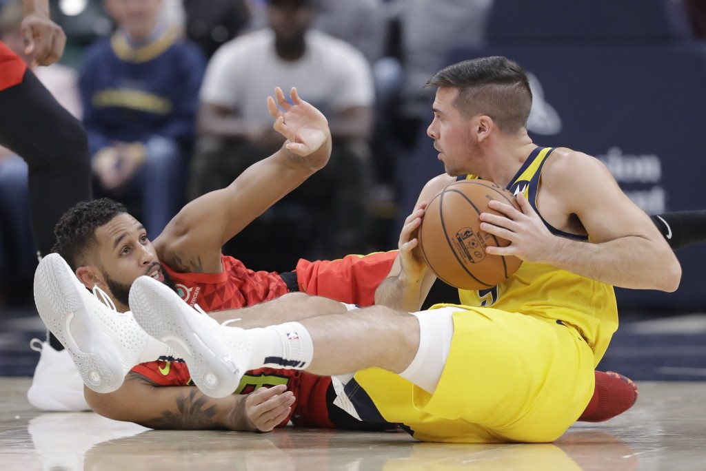 Indiana Pacers' T.J. McConnell (9) recovers a loose ball against Atlanta Hawks' Allen Crabbe (33) during the first half of an NBA basketball game, Fri...