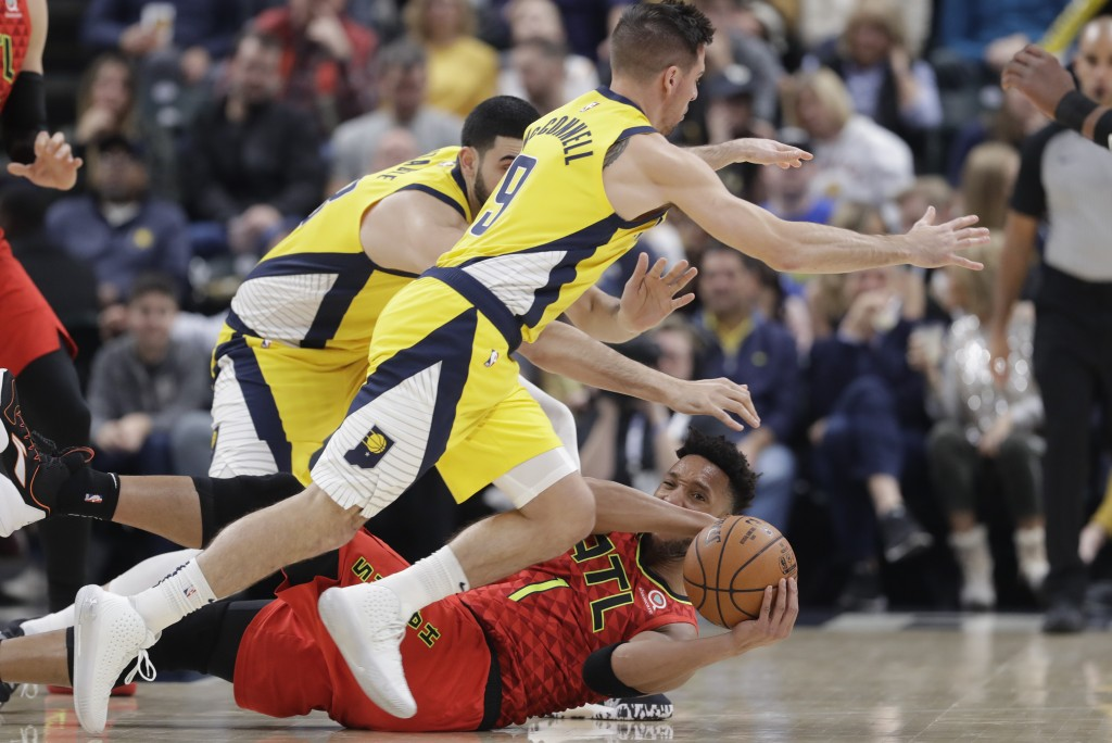 Atlanta Hawks' Evan Turner (1) makes a pass while being defended why Indiana Pacers' T.J. McConnell (9) and Goga Bitadze (88) during the first half of...