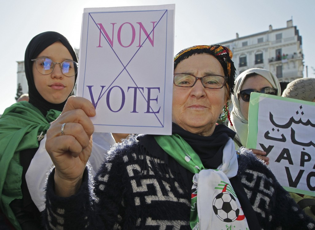 """An Algerian demonstrator holds a placard that reads """"no vote"""" as she stage a protest against the government and the upcoming presidential elections in..."""