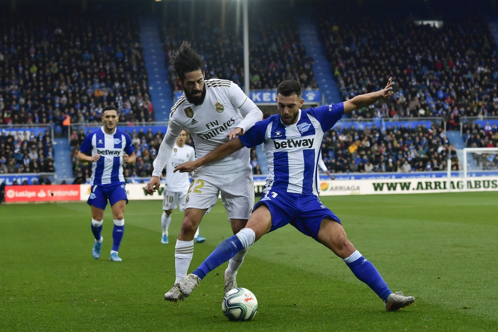 Real Madrid's Isco, left, duels for the ball with Alaves' Luis Rioja during the Spanish La Liga soccer match between Real Madrid and Alaves at Mendizo...