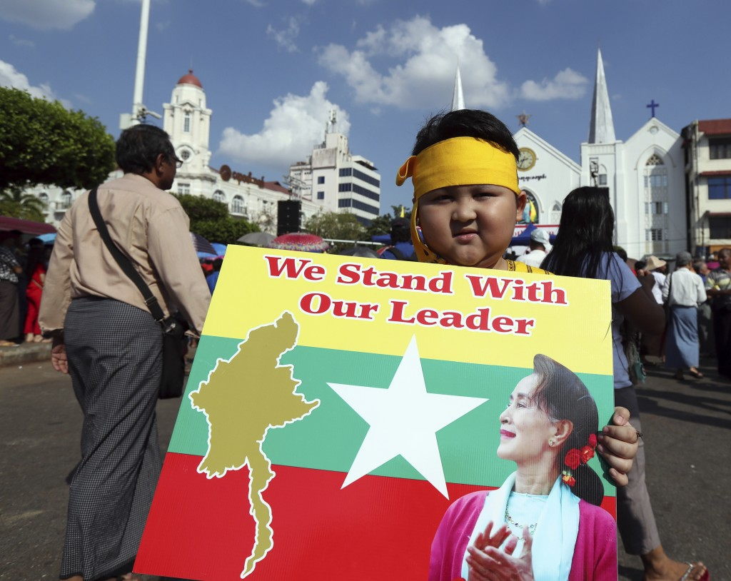 A boy with Karen ethnic attire holds placard with picture of Myanmar leader Aung San Suu Kyi during a rally Sunday, Dec. 1, 2019, in Yangon, Myanmar. ...