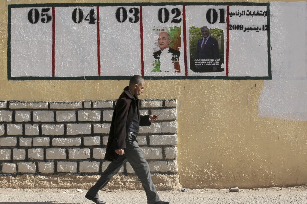 In this Nov. 18, 2019, photo, a man walks past empty or defaced electoral posters in Ain Soussera, south of Algiers. Algeria's presidential campaign i...