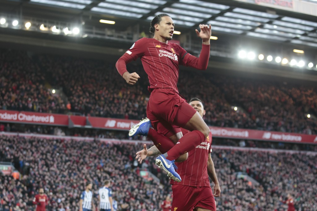 Liverpool's Virgil van Dijk celebrates after scoring during the English Premier League soccer match between Liverpool and Brighton at Anfield Stadium,...