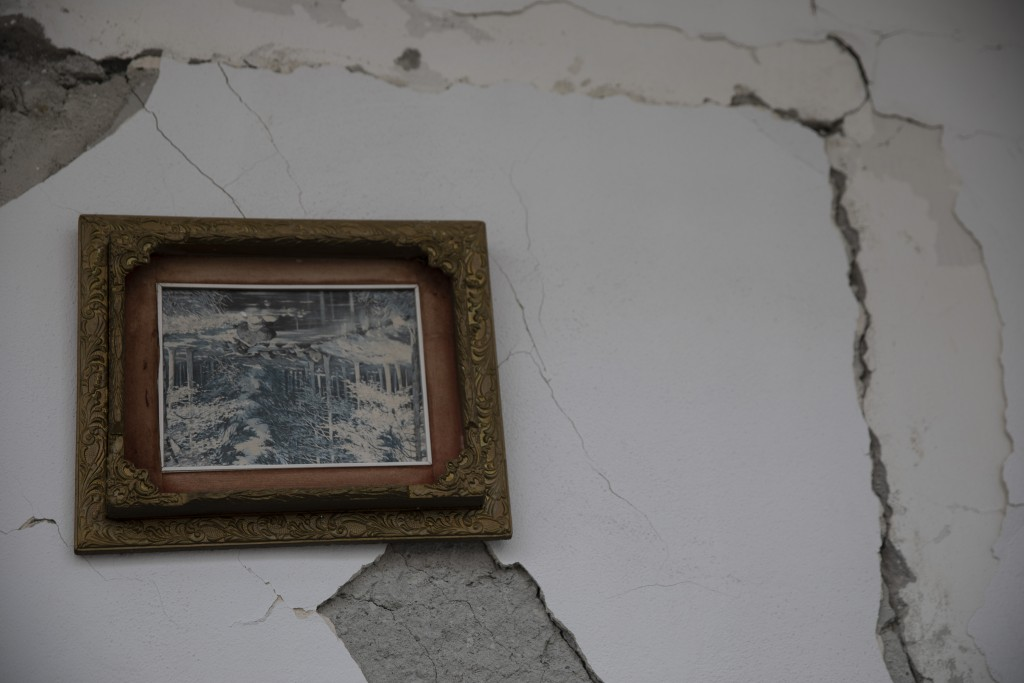 In this Thursday, Nov. 28, 2019 photo a frame which has turned up side down on a wall of a damaged building in Durres, western Albania following a dea...