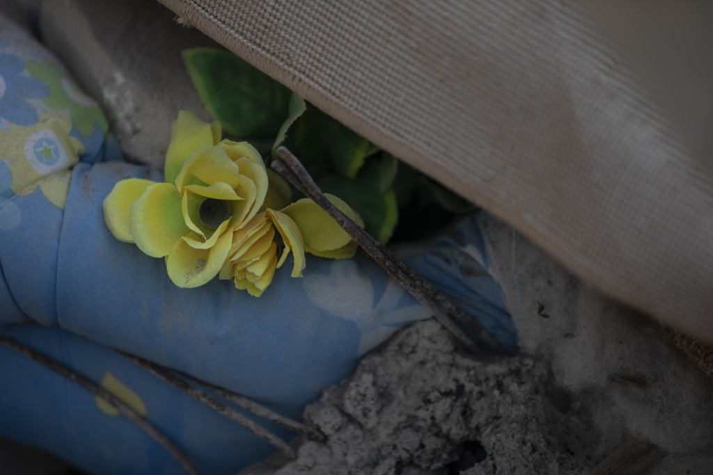 In this Wednesday, Nov. 27, 2019 photo, a plastic flower among rubbles of a collapsed building damage building in Thumane, western Albania following a...