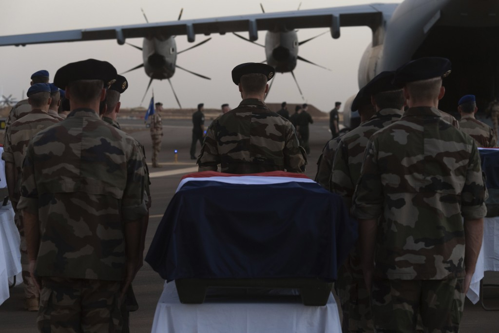 In this Saturday, Nov. 30, 2019 photo provided by French Defense Communication and Audiovisual Department (ECPAD), soldiers stand guard by the coffins...