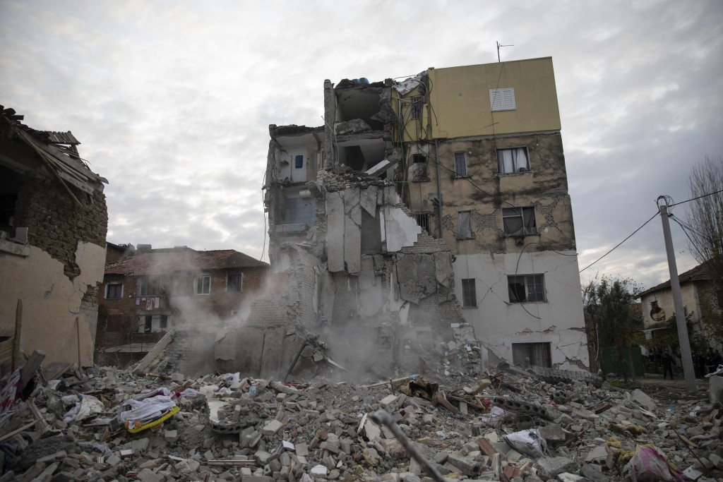 In this Wednesday, Nov. 27, 2019 photo, dust rises from the falling parts of a destroyed building during an aftershock in Thumane, western Albania. Th...