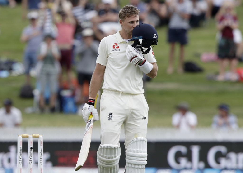 England's Joe Root kisses his helmet as he celebrates after scoring a century during play on day three of the second cricket test between England and ...