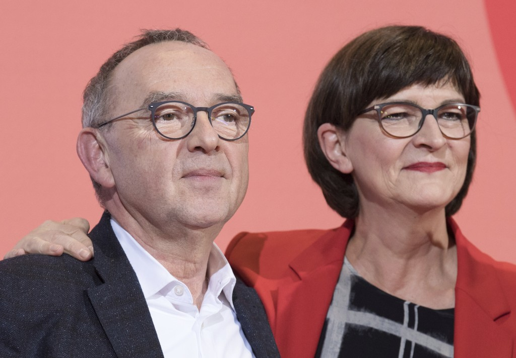 Norbert Walter-Borjans, left, and Saskia Esken stand on the podium after winning the member voting of the Social Democratic Party, SPD, chairmanship a...