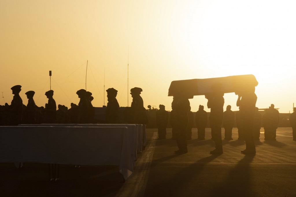 In this Saturday, Nov. 30, 2019 photo provided by French Defense Communication and Audiovisual Department (ECPAD), soldiers carry the coffin of one of...