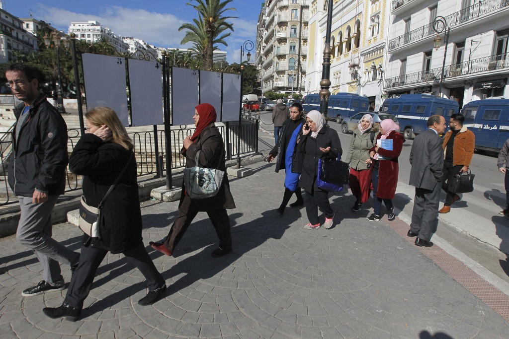 In this Nov. 17, 2019, photo, people walk past empty electoral boards, in Algiers. Algeria's presidential campaign is in trouble. Candidates are strug...