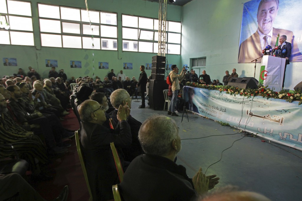 FILE - In this Nov. 19, 2019, file photo, people listen to former Algerian Prime Minister Ali Benflis campaigns for the upcoming presidential election...
