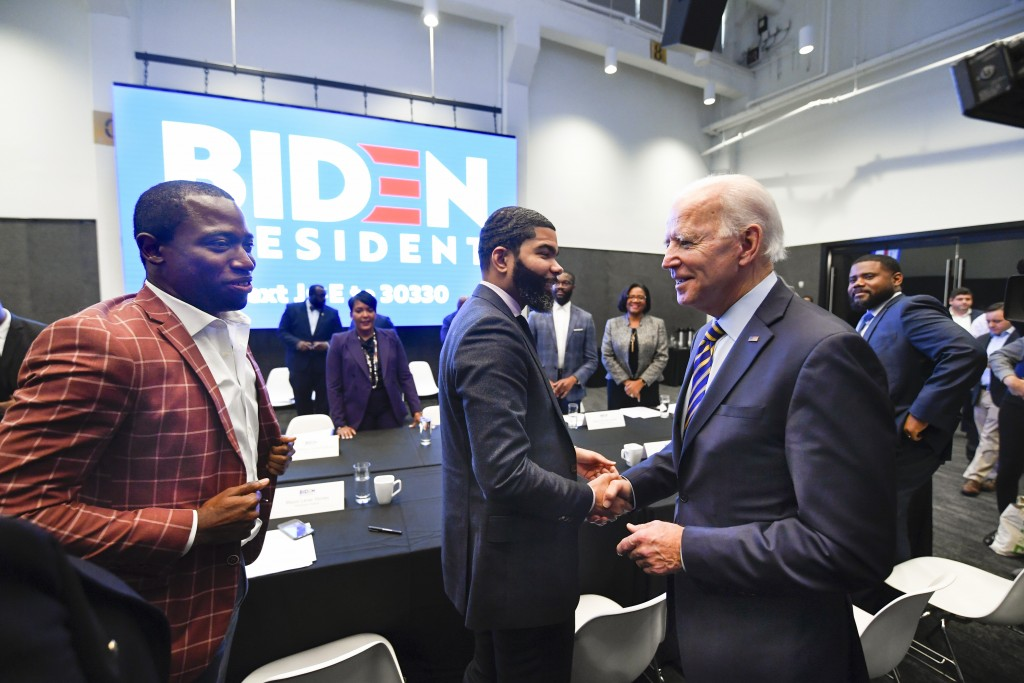FILE - In this Nov. 21, 2019, file photo, Democratic presidential candidate former Vice President Joe Biden, right, walks around a table meeting with ...