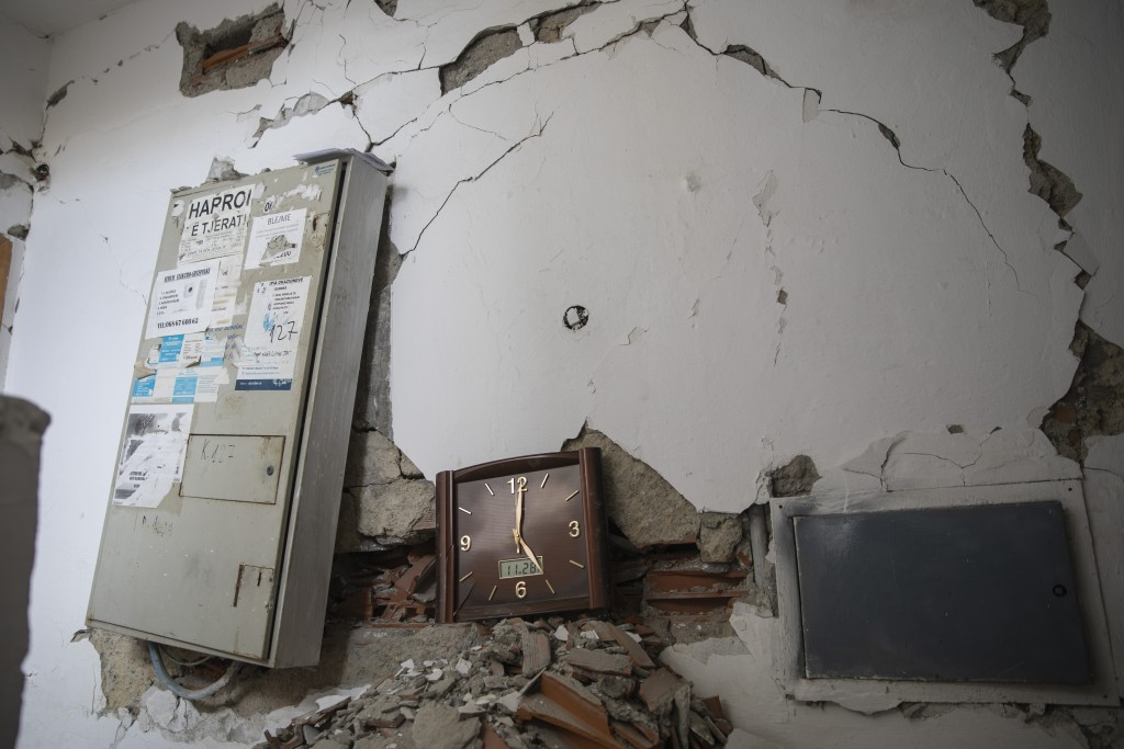 In this Thursday, Nov. 28, 2019 photo, a wall clock that was stoped working during the time of the deadly earthquake that struck in Albania early Tues...