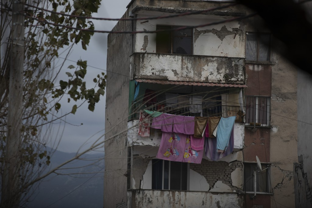 In this Wednesday, Nov. 27, 2019 photo, laundry hangs on a line from a damaged building in Thumane, western Albania following a deadly earthquake. A h...