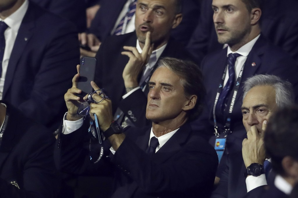 Italy coach Roberto Mancini takes pictures while waiting for the start of the draw for the UEFA Euro 2020 soccer tournament finals in Bucharest, Roman...