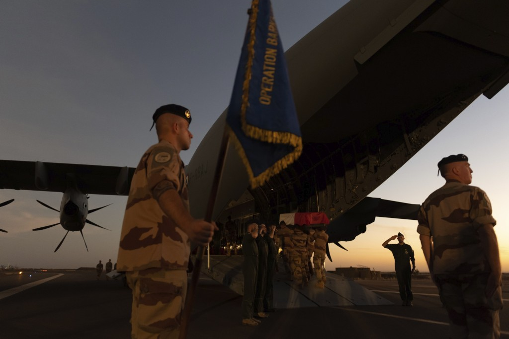 In this Saturday, Nov. 30, 2019 photo provided by French Defense Communication and Audiovisual Department (ECPAD), soldiers salute as the coffins of t...