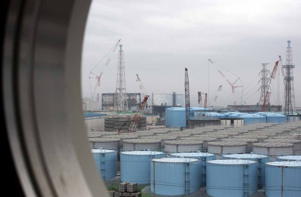 FILE - In this Feb. 23, 2017, file photo, storage tanks for contaminated water are seen through a window of a building during a media tour to the tsun...