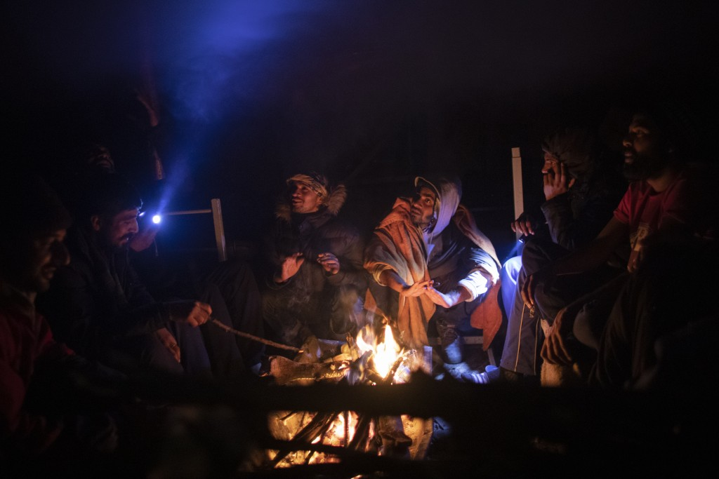 Migrants sit around fire inside a tent at the Vucjak refugee camp outside Bihac, northwestern Bosnia, Sunday, Dec. 1, 2019. Despite the approach of ha...