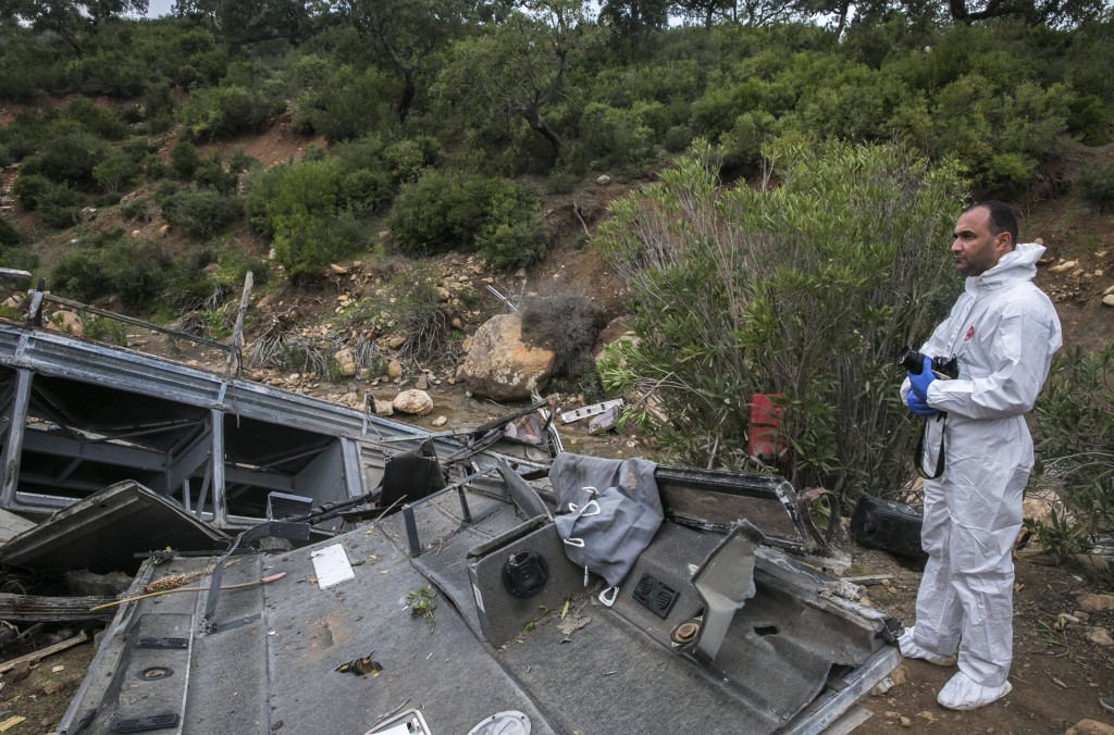 A police investigator stands by a regional bus that crashed off a hill Sunday Dec.1, 2019, killing at least 22 local passengers who were on an excursi...