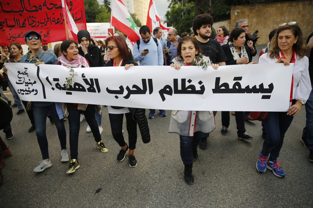 "Lebanese protesters carry an Arabic banner that reads, ""Down with the civil war regime,"" as they march in Beirut, Lebanon, Sunday, Dec. 1, 2019. Prote..."
