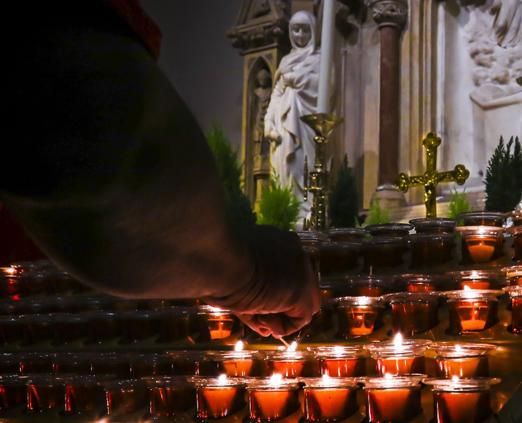 In this Wednesday, Nov. 27, 2019, photo, a Catholic faithful lights candles at a prayer station during a visit to one of the great symbols of the Roma...