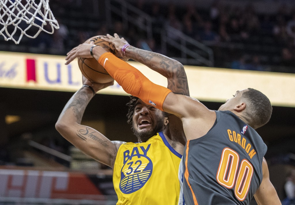 Golden State Warriors forward Marquese Chriss (32) is tightly defended by Orlando Magic forward Aaron Gordon (00) during the first half of an NBA bask...