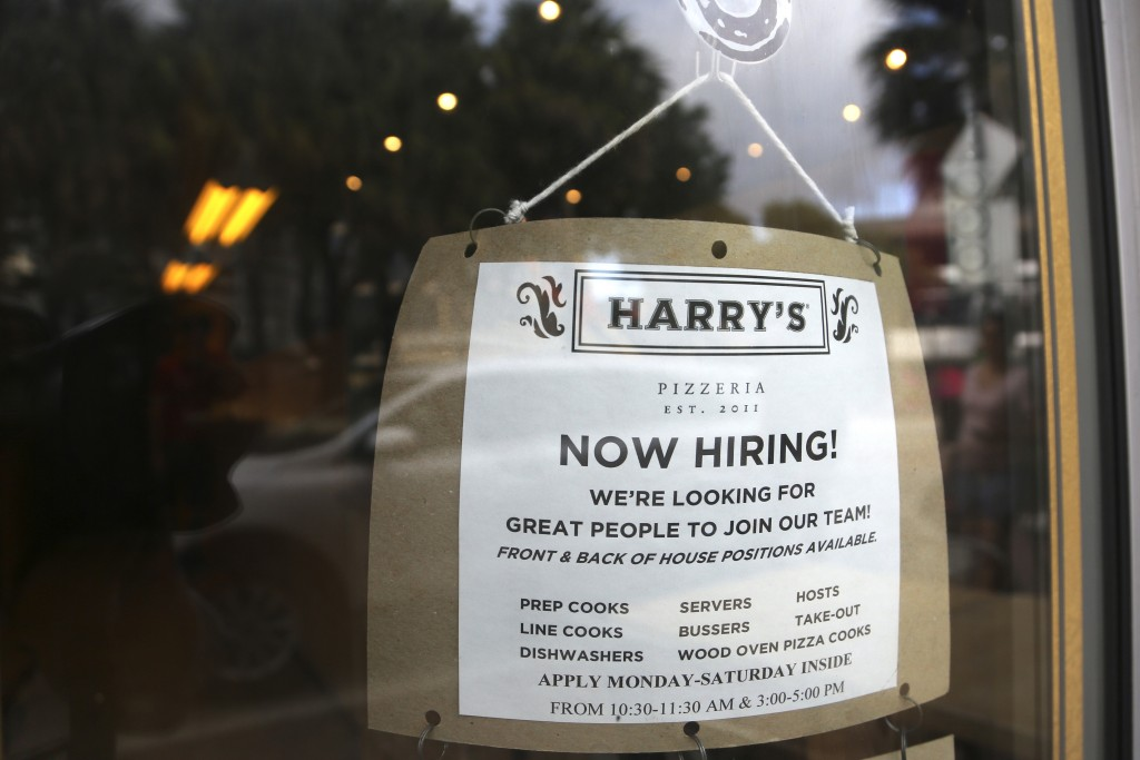 FILE - In this Nov. 6, 2019, file photo a sign advertises job opportunities at Harry's Pizzeria in the Coconut Grove neighborhood in Miami. Economists...