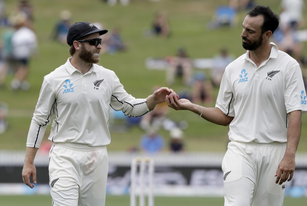 New Zealand's Kane Williamson, left, hands the ball to bowler Daryl Mitchell during play on day four of the second cricket test between England and Ne...