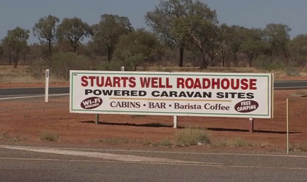 In this image made from video, an advertisement for the campsite line the roadside where a woman was found after being stranded in the Alice Springs a...