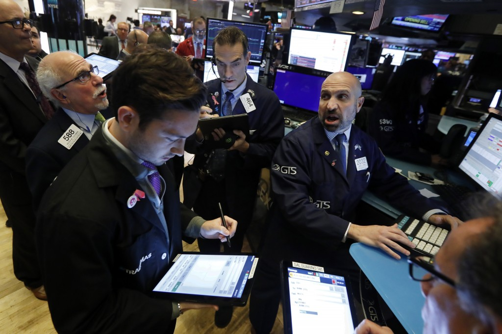 FILE - In this Nov. 14, 2019, file photo specialist James Denaro, right, works with traders at his post on the floor of the New York Stock Exchange. T...