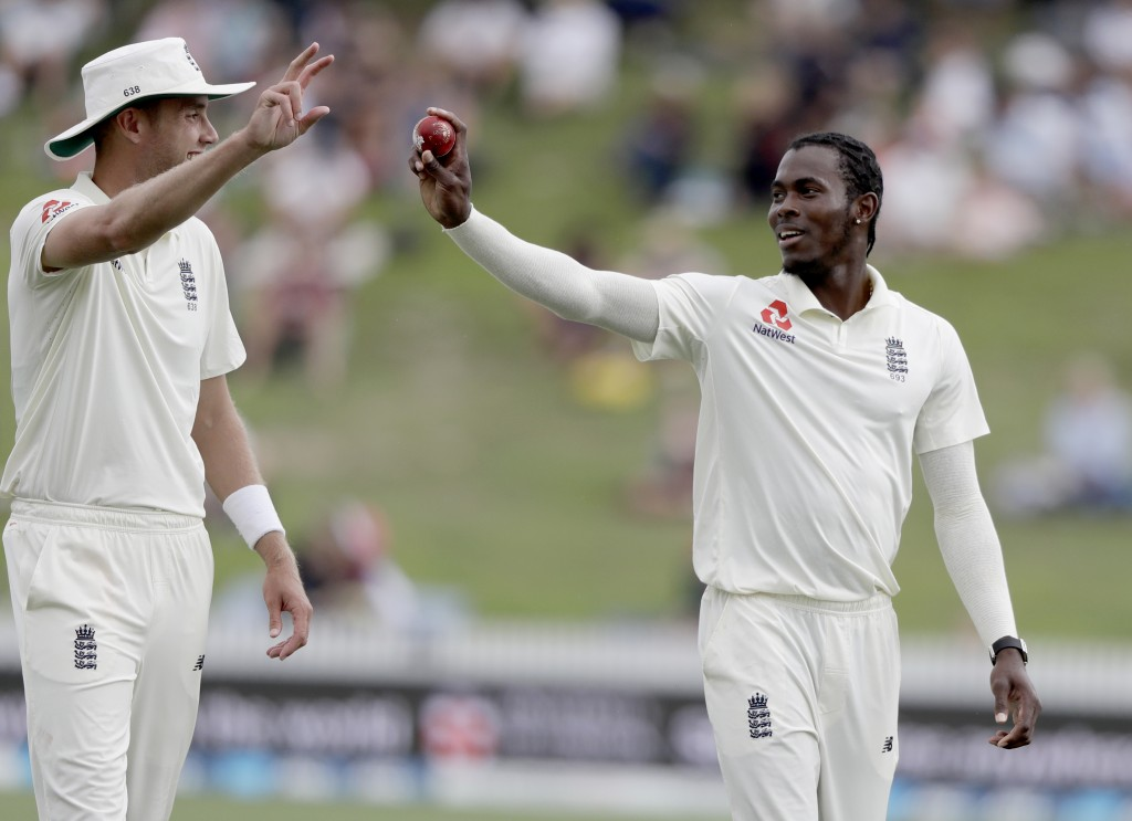 England's Jofra Archer, right, shows the ball to teammate Stuart Broad during play on day four of the second cricket test between England and New Zeal...