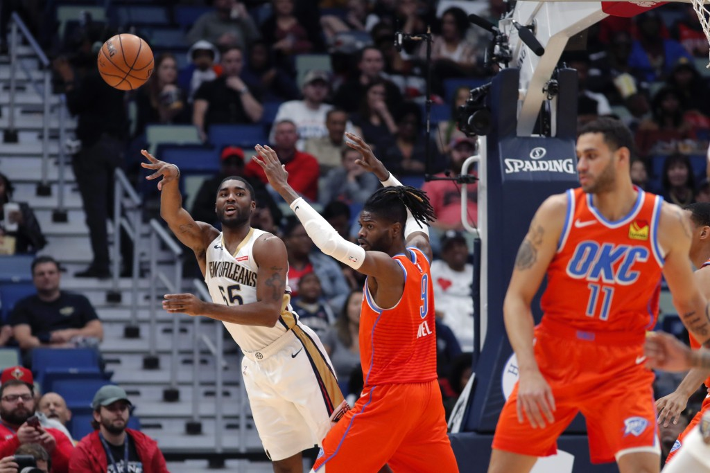 New Orleans Pelicans guard E'Twaun Moore (55) passes around Oklahoma City Thunder center Nerlens Noel (9) in the first half of an NBA basketball game ...