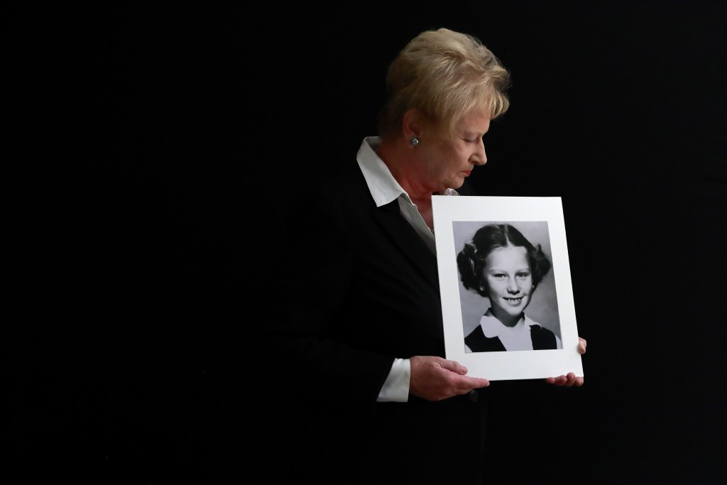 In this Nov. 20, 2019, photo, Nancy Holling-Lonnecker, 71, poses with a picture taken of her as a young girl, at her home in San Diego. Holling-Lonnec...