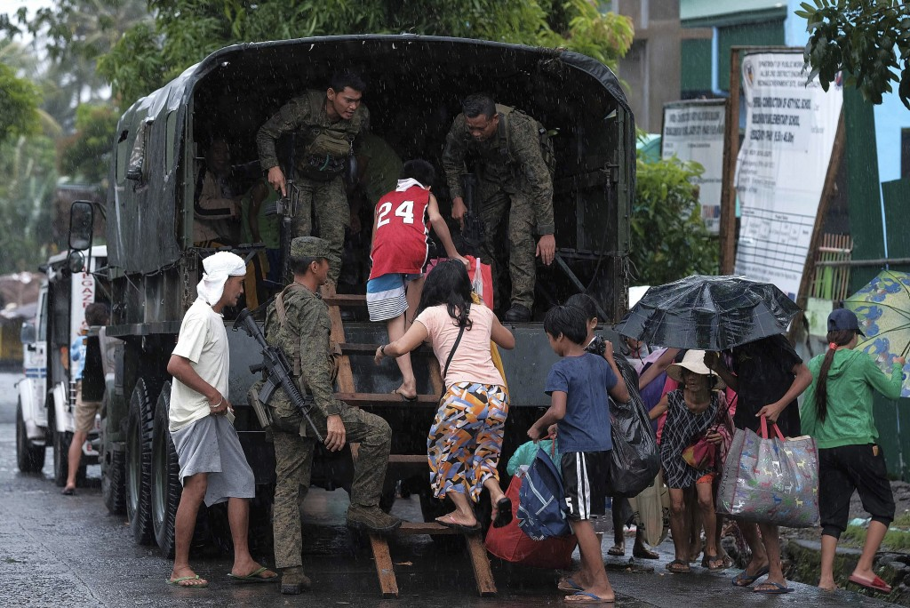 Residents ride a military truck as they evacuate to safer grounds in preparation for the coming of Typhoon Kammuri in Legazpi, Albay province, southea...