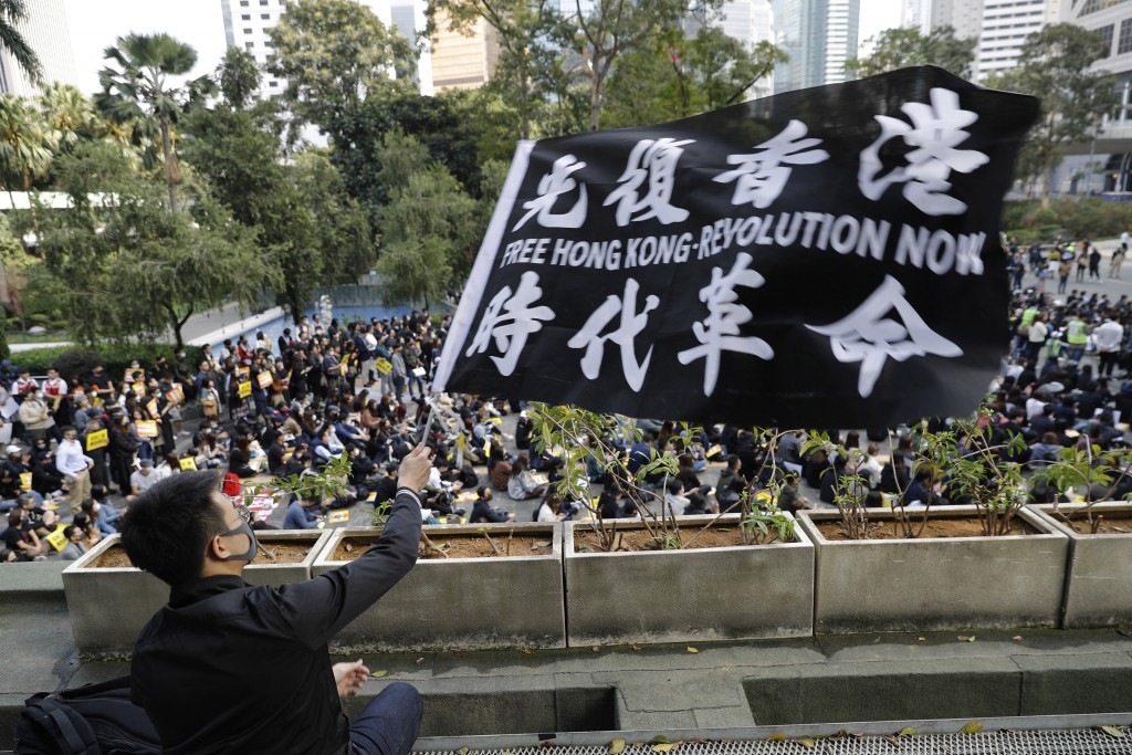 A pro-democracy supporter waves a flag during a rally by the advertising industry in Hong Kong on Monday, Dec. 2, 2019. Thousands of people took to Ho...