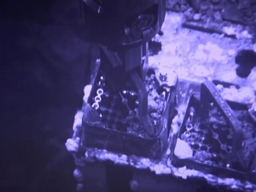 FILE - This April 15, 2019, file image released by Tokyo Electric Power Co. (TEPCO) shows an operation to remove fuel from a cooling pool at Unit 3 of...