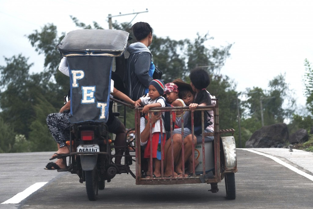 Residents ride a pedicab as they evacuate to higher grounds in preparation for the coming of Typhoon Kammuri in Legazpi, Albay province, southeast of ...