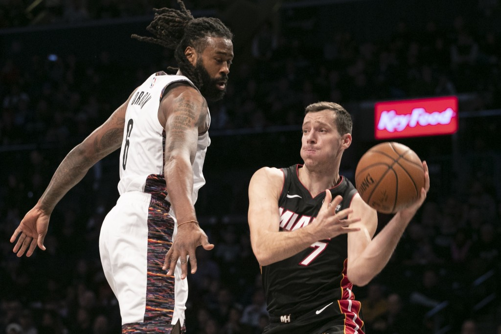 Brooklyn Nets center DeAndre Jordan (6), left, tries to block a pass by Miami Heat guard Goran Dragic (7) in the first half of an NBA basketball game,...
