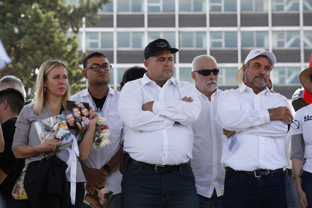Adriana LeBaron, left, Julian LeBaron, center, and Adrian LeBaron, right, stand during a protest against the first year in office of Mexico's Presiden...
