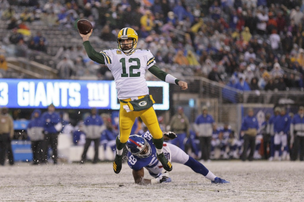 Green Bay Packers quarterback Aaron Rodgers throws a touchdown pass to Marcedes Lewis during the second half of an NFL football game against the New Y...