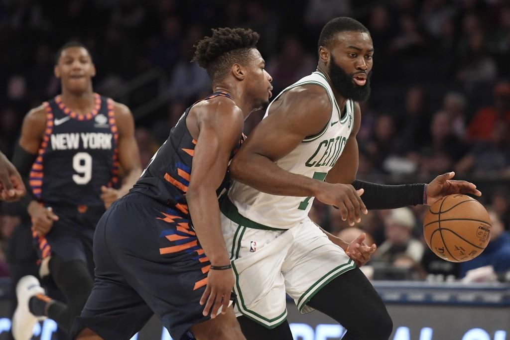 Boston Celtics guard Jaylen Brown (7) dribbles as New York Knicks guard Dennis Smith Jr. (5) defends during the second half of an NBA basketball game,...